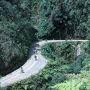 """Mountain Biking on Death Road, Bolivia...A tour group of Mountain Bikers bike down the infamous narrow dirt road, most of the road no wider than 3.2meter's, is cut into the side of the mountain with sheer drops to the left of up to 600 meter's with virtually no safety rails on the winding steep decent...The North Yugas Road is a 64 Kilometer road leading from La Paz to Corioico. It is legendary for it's extreme danger and in 1995 the Inter American Development Bank christened is as the """"world's most dangerous road"""".. The road was built in the 1930's during the Chaco War by Paraguayan prisoners to connect the Amazon rainforest region of Northern Bolivia to it's capital City La Paz. One estimate is that 200 to 300 travelers were killed yearly along the road. On 24 July 1983, a bus veered off the Yungas Road and into a canyon, killing more than 100 passengers in what is said to be Bolivia's worst road accident..A new stretch of the La Paz-Coroico highroad was opened in 2006 to bypass the notorious stretch known as death road..The danger of the road has now made it a popular tourist destination starting in the 1990's and drawing thrill-seekers and mountain bike enthusiasts who ride on the 64km mainly downhill stretch from La Cumbre, a 4,700 meter peak to Yolosa, a decent of 3600 meter's (11,800 feet). The journey includes breathtaking views of snow covered peaks and towering cliffs and starts along modern asphalted road before entering the jungle itself and the most dangerous and notorious part of the ride. The infamous narrow dirt road, most of the road no wider than 3.2meter's, is cut into the side of the mountain with sheer drops to the left of up to 600 meter's with virtually no safety rails on the winding steep decent..There are now many tour operators catering to this activity, providing information, guides, transport and equipment. Nevertheless, the Yungas Road remains dangerous. At least 13 of these cyclists died on the ride since 1998, the latest A 28-year-ol"""
