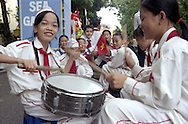 School parade in Hanoi, Vietnam, Asia. A vietnamese girl beat the drum and smile to the camera.