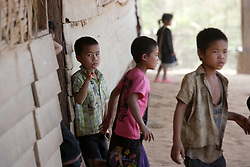 Unnamed children leaving class at lunch time. At the primary school which is close to the SCI preschool. He is following the teacher's prompts, and reading from the blackboard.    Ban Nong Paad, Vienthong District, Bolikhamxai Province, Lao PDR