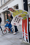 Waiting for a green light to cross the road, an adult man guides a young boy on his bike, alongsiode a construction industry warning sign, erected to warn pedestrians, but damaged so that it is seemingly bending over at the waist, on 8th March 2021, in London, England.
