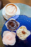 Baked and Wired, a bakery and coffee and tea house in Georgetown, Washington, DC, offers up home made desserts and gourmet coffee..Pictured here is a cappuccino, a strawberry cupcake, chocolate cupcake and German Chocolate cupcake, all served in parchment cups.