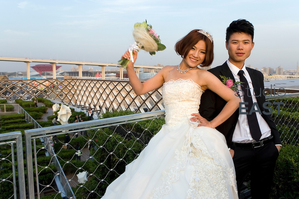 Newlyweds Zhao Xia (left) and Lin Hua (right) celebrate their wedding on the roof of the French Pavilion at Shanghai World Expo 2010, in Shanghai, China, on May 11, 2010. France Pavilion at Expo 2010 organized for the first time today French Romantic Weddings, allowing Chinese new couples to tie the knot in the beautiful French-style garden within the pavilion. Photo by Lucas Schifres/Pictobank