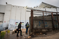 1 March 2020, Bethlehem: 'Hope' and 'Smile' read texts on the separation wall, noted under drawings of two Palestinian flags, as people enter into Checkpoint 300, where tens of thousands of Palestinians, most of them working in construction and maintenance, cross from Bethlehem to Jerusalem in the mornings.