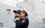 An officer from the Chinese Naval assault ship Chang Bai Shan takes pictures aboard at Portsmouth Royal Navy Base today. The ship is involved in the first visit by the Chinese Navy to the UK since 2007 and the largest ever. She is accompanied by the frigate Yun Cheng and the replenishment ship Chaohu. The ships arrived in Portsmouth 24 hours early due to the expected bad weather. The Royal Navy statement stated that the five day formal visit is aimed at enhancing military understanding between the UK and China. Picture date Monday 12th January, 2015.<br /> Picture by Christopher Ison. Contact +447544 044177 chris@christopherison.com