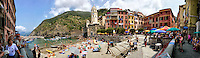 Photo of the Vernazza Church of Santa Margherita d'Antiochia, tower houses, marina and beach, Italy.