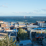 A strong wind whips up whitecaps on the Strait of Magellan as seen over the rooftops of Punta Arenas, Chile. The city is the largest south of the 46th parallel south and capital city of Chile's southernmost region of Magallanes and Antartica Chilena.