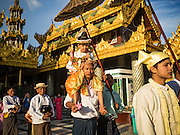 31 OCTOBER 2015 - YANGON, MYANMAR: A boy being ordained as a Buddhist novice (young monk) with some of his family at Shwedagon Pagoda. Shwedagon Pagoda is officially known as Shwedagon Zedi Daw and is also called the Great Dagon Pagoda or the Golden Pagoda. It is a 99 metres (325 ft) tall pagoda and stupa located in Yangon, Burma. The pagoda lies to the west of on Singuttara Hill, and dominates the skyline of the city. It is the most sacred Buddhist pagoda in Myanmar and contains relics of four past Buddhas: the staff of Kakusandha, the water filter of Koṇāgamana, a piece of the robe of Kassapa and eight strands of hair from Gautama, the historical Buddha. The pagoda was built between the 6th and 10th centuries by the Mon people, who used to dominate the area around what is now Yangon (Rangoon). The pagoda has been renovated numerous times through the centuries. Millions of Burmese and tens of thousands of tourists visit the pagoda every year, which is the most visited site in Yangon.      PHOTO BY JACK KURTZ