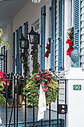 Christmas decorations on a porch, known locally as a piazza, of a Charleston Single style historic home  in Charleston, South Carolina.