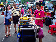 24 JULY 2018 - BANGKOK, THAILAND: Asian tourists buy grilled sweet corn from a vender on Khao San Road in Bangkok. Khao San Road is Bangkok's original backpacker district and is still a popular hub for travelers, with an active night market and many street food stalls. The Bangkok municipal government plans to shut down the street market by early August because city officials say the venders, who set up on sidewalks and public streets, pose a threat to public safety and could impede emergency vehicles. It's the latest in a series of night markets and street markets the city has closed.   PHOTO BY JACK KURTZ