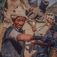 Tamang villagers load baskets they will carry as porters in the foothills of the Nepal Himalaya.