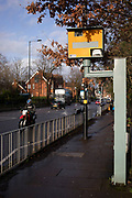 Motorcycle passing a yellow speed camera in Wake Green on 16th Febuary 2020 in Birmingham, United Kingdom.  A traffic enforcement camera is a camera which may be mounted beside or over a road or installed in an enforcement vehicle to detect traffic regulation violations, including speeding.