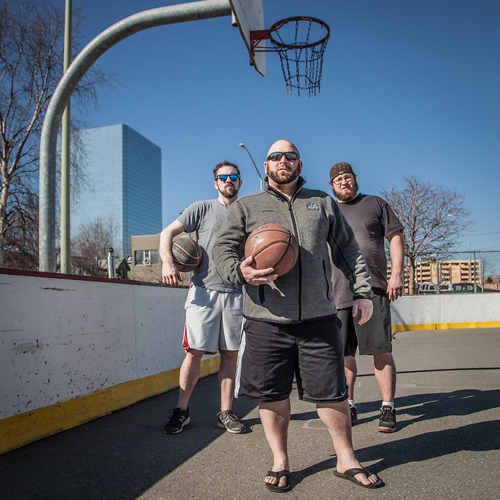 """Mark Hoffman (left), Greg Conners (center), and J.C. Durate (right) at the Delaney hockey rink and basketball court, Anchorage  """"We all met while working at the Glacier Brew House…we're all still in the hospitality business""""  hoffsox@yahoo.com"""