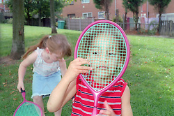 Young boy holding a tennis racket up to his face,