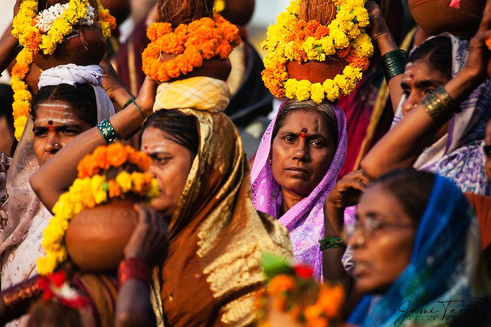 A group of women following a holy man come to pray at the Ganges River on a step of the main Dasaswamedh Ghat in Varanasi, Varanasi, Uttar Pradesh, India
