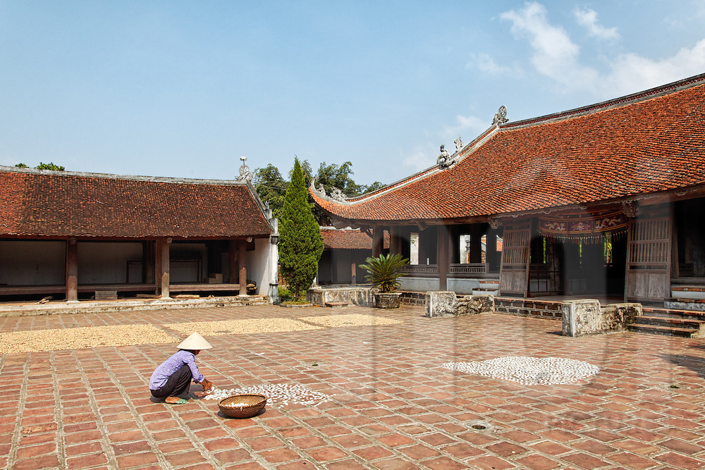 A Vietnamese woman works in the courtyard outside Mong Phu communal house in Duong Lam Village, Son Tay Town, outskirts of Hanoi, Vietnam, Southeast Asia. The ancient village has a history of about 1,200 years and contains 5 villages. The God Tan Vien Son is worshiped in this communal house.