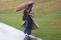© Licensed to London News Pictures. 27/09/2021. London, UK. A woman shelters under an umbrella as she walks in Greenwich Park during a rain shower .Rain showers are forecasted to continue in parts of London and South East England for the rest of the week.  Photo credit: George Cracknell Wright/LNP