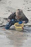 Young girl playing in the sand at the beach.