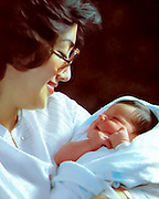 A nurse holds a newborn baby in a hospital maternity ward