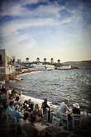 People at a restaurant, overlooking the Aegean sea, view of the windmills in Mykonos, Greece