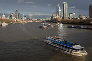 Looking eastwards downriver from Waterloo Bridge to the Southbank and the City of London, a burst of sunlight shines across river traffic, from the top of the One Blackfriars skyscraper, on 4th March 2019, in London England.