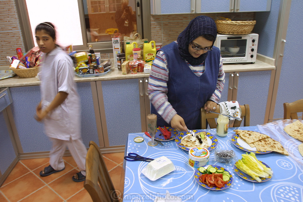 (MODEL RELEASED IMAGE). Because 98 percent of the food in Kuwait is imported, Wafaa Al Haggan's kitchen is a snapshot of the world's market basket. Hungry Planet: What the World Eats (p. 200).