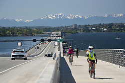 United States, Washington, Bellevue, cyclists on bike path on SR 520 floating bridge, with Olympic Mountains in distance