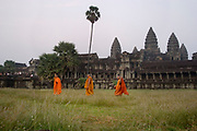 Buddhist monks walk  through the grass behind the retaiing wall during sunset at Angkor Wat. This jewel in the crown of Angkor's ancient temples is a vision of beauty, might and Khmer architectural excellence. The five towers dominate the view, which you are led to trough outer walls, along causeways over the moat and past the two giant pools which act as a mirror of the vision. Consecrated at around 1150 to the Hindu god, Vishnu it is suggested that construction took 30 years.