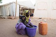 Hassania Issah, 30, carries her son Souleyman Ali, 1, who is recovering from malnutrition, on her back while doing laundry at a UNICEF-sponsored therapeutic feeding center at the Mongo hospital in the town of Mongo, Guera province, Chad on Tuesday October 16, 2012.