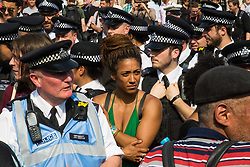 London, June 21st 2017. Protesters march through London from Sheherd's Bush Green in what the organisers call 'A Day Of Rage' in the wake of the Grenfell Tower fire disaster. The march is organised by the Movement for Justice By Any Means Necessary and coincides with the Queen's Speech at Parliament, the destination. PICTURED: Police attempt to remove protesters from the road.