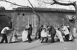 People having haircuts in the street in a Beijing hutong in China