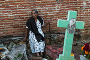 An elderly Mexican woman at the gravesite of relatives for Day of the Dead festival known in Spanish as Día de Muertos at the old cemetery October 31, 2013 in Xoxocotlan, Mexico. The festival celebrates the lives of those that died.