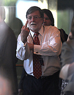 Defense attorney Cheney Mason, center, gestures toward reporters and spectators peering through a restaurant window, across the street from the Orange County Courthouse, while trying to get a glimpse of the Casey Anthony defense team celebrating after the not-guilty verdict was announced in Orlando, Fla., Tuesday, July 5, 2011.(AP Photo/Phelan M. Ebenhack)