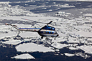 Helicopter flying over broken pack ice to the remote island of Peter 1 Øy (on the Phantom Coast of Antarctica) from the icebreaker Kapitan Khlebnikov,