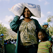 "Geraldine Richards thirty-four, aid queue, Petion-Ville, with her sisters remaining child, Giodania. Geraldine is a jewellery seller. She has five kids, all boys  (twins and triplets), as did her sister prior to the earth quake but only one of her sister's children survived (Giodania, pictured) when their house collapsed in the earthquake. ""My sister  is so depressed she hasn't eaten. She lost her husband and  all but one of her five  kids. She hasn't even recovered the bodies. It's necessary to bury our loved ones but the government cleared them away in huge trucks and dumped them in mass graves or they were burnt.  She  has no will to live, she is suicidal. I am looking after her and her kid, one of the bags of food I have is for my sister. I am lucky to get this, if you miss the card distribution you are lucky to get food and getting back with the food is difficult sometimes. The men take it or someone will cut the bag and catch the rice in a bucket, before you realise. All the same, we are thankful for the aid."""