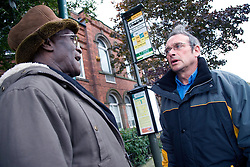Two friends chatting whilst waiting at the bus stop,