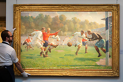 """© Licensed to London News Pictures. 01/06/2018. LONDON, UK. A Sotheby's technician presents """"Football Match"""", 1949, by Andrei Vasilevich Korotkov (Est. GBP60-80k) at a preview of the Russian Pictures and Russian Works of Art, Fabergé & Icons sale which will take place at Sotheby's, New Bond Street on 5 June.  Photo credit: Stephen Chung/LNP"""