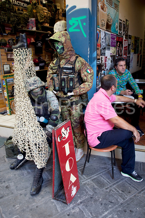 Shop selling military clothes and equipment stands in sinister mood next to a cafe where men sit talking together in Monastiraki Flea Market shopping area. Monastiraki (little monastery) is a flea market neighborhood in the old town of Athens, and is one of the principal shopping districts in the capital. The area is home to clothing boutiques, souvenir shops, and specialty stores, and is a major tourist attraction in Athens and Attica for bargain shopping. The area is named after Monastiraki Square, which in turn is named for the Pantánassa church monastery that is located within the square. Athens is the capital and largest city of Greece. It dominates the Attica periphery and is one of the world's oldest cities, as its recorded history spans around 3,400 years. Classical Athens was a powerful city-state. A centre for the arts, learning and philosophy.