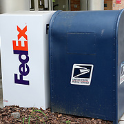 Federal Express and US Postal Service drop boxes are seen outside a business in downtown Orlando on Monday, March 30, 2020 in Orlando, Florida. (Alex Menendez via AP)