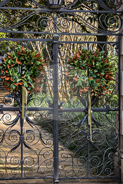 Magnolia Christmas wreaths decorate the Sword Gate on a historic home at Legare Street in Charleston, SC.