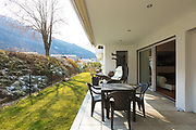 Small veranda with garden furnished with outdoor furniture. Winter day