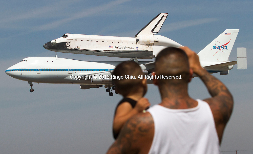 Spectators Mario Vasquez, 40, of Redondo Beach and his son Mario Jr., 2, watch as space shuttle Endeavour, atop NASA's Shuttle Carrier Aircraft, prepares to land at LAX in Los Angeles, Calif., on Friday, September 21, 2012.   (Photo by Ringo Chiu/PHOTOFORMULA.com)