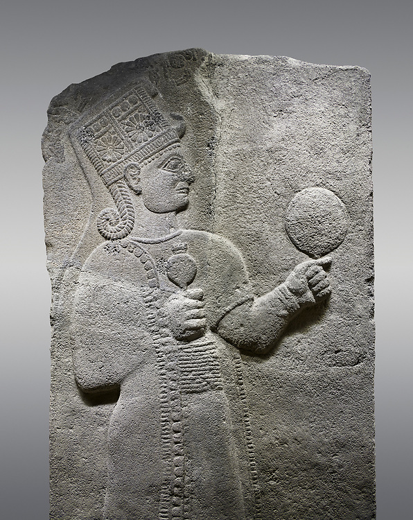 Picture & image of Hittite relief sculpted orthostat stone panel of Long Wall Basalt, Karkamıs, (Kargamıs), Carchemish (Karkemish), 900 - 700 B.C. Anatolian Civilizations Museum, Ankara, Turkey.<br /> <br /> Goddess Kubaba. Goddess is depicted from the profile. The part below the chest of the relief is broken. She holds a pomegranate in her hands on her chest. She carries a one-horned headdress on her head. Her braided hair hangs down to her shoulder. The text in the hieroglyphics is not understood. The lower part of the relief has been restored. <br /> <br /> On a gray background. .<br />  <br /> If you prefer to buy from our ALAMY STOCK LIBRARY page at https://www.alamy.com/portfolio/paul-williams-funkystock/hittite-art-antiquities.html  - Type  Karkamıs in LOWER SEARCH WITHIN GALLERY box. Refine search by adding background colour, place, museum etc.<br /> <br /> Visit our HITTITE PHOTO COLLECTIONS for more photos to download or buy as wall art prints https://funkystock.photoshelter.com/gallery-collection/The-Hittites-Art-Artefacts-Antiquities-Historic-Sites-Pictures-Images-of/C0000NUBSMhSc3Oo