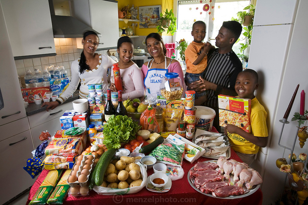 Maria Natercia Lopes-Furtado and her husband Ernesto Lopes Sanchez from Cabo Verde in the kitchen of their home in Rodange, Luxembourg with one week's worth of food.  The children are Darlene, Melody, Teddy, and Lionel. Model Released. The image is part of a collection of images and documentation for Hungry Planet 2, a continuation of work done after publication of the book project Hungry Planet: What the World Eats.