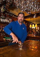 """Ray Simanson pours a glass of scotch in his bar at Tavern 27 to promotes the """"Exquisite Scotch Flight"""" an upcoming event later this month.  (Karen Bobotas/for the Laconia Daily Sun)"""