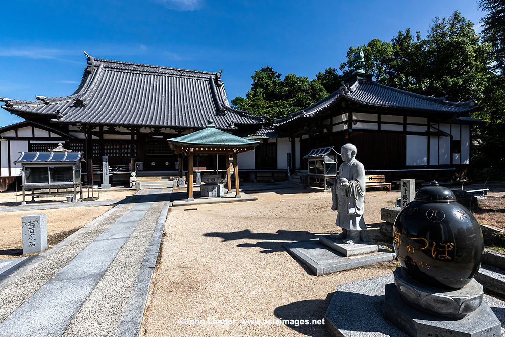 Iyo Kokubunji Temple is No. 59 on the Shikoku pilgrimage.  This is the only temple on the pilgrimage belonging tothe Shingon Ritsu Sect. Itwas founded in 807 byKoboDaishi, the founder of the pilgrimage,who carved the statue of Enmei Jizo Bosatsu. This deity is called the Helmsman Jizo, and fishermen believe that it protects them at sea. In the main hall there are thousands of small statues of Jizo donated by pilgrims from all over Japan. In the hands of each statue is a ship's wheel  There is a statue of Kobo Daishi on the grounds near the medicine ball, with which you can shake hands.