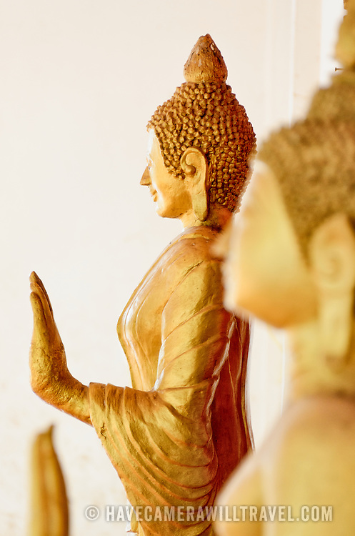 Golden statues of The Buddha at a Wat (Buddhist Temple) in Vientiane, Laos. This statue is in the Cambodian style. Focus is on the statue in the background with shallow depth of field.