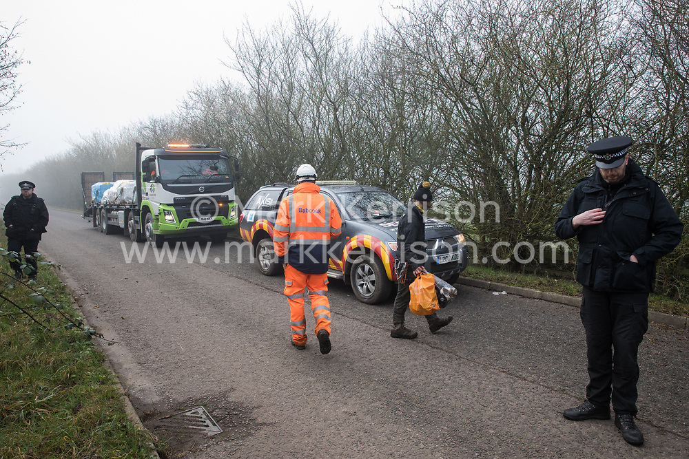 Denham, UK. 6 February, 2020. Police officers monitor environmental activists from Save the Colne Valley, Stop HS2 and Extinction Rebellion walking at a snail's pace along a road so as to block for several hours a security vehicle and truck delivering fencing and other supplies to be used for works associated with the HS2 high-speed rail link close to the river Colne at Denham Ford. Some activists also collected litter during the action.