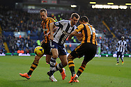 West Brom's Gareth McAuley © is stopped by Hull city's David Meyler (l) and Jake Livermore ®. Barclays Premier league, West Bromwich Albion v Hull city at the Hawthorns in West Bromwich, England on Saturday 21st Dec 2013. pic by Andrew Orchard, Andrew Orchard sports photography.