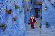 Two young, traditionally dressed, Moroccan men great each other in the old town (medina) of Chefchaouen in Morocco.