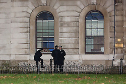 © Licensed to London News Pictures. 29/12/2015. London, UK. Police officers speak to an activist through a window of the Royal Mint building. Squatters have occupied the Royal Mint building, located opposite the Tower of London on the border of the City of London to protest against homelessness and highlight how empty buildings could provide shelter for rough sleepers. The site was previously used to manufacture British coins but is currently vacant and activists argue that this along with other vacant commercial buildings could be used to provide short term shelter for the homeless. Photo credit : Vickie Flores/LNP